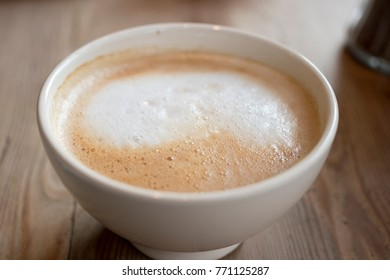 Closeup image of a coffee latte in a white bowl on a wooden table.