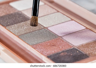 Closeup image of a colorful shadow eye palette with a small brush.