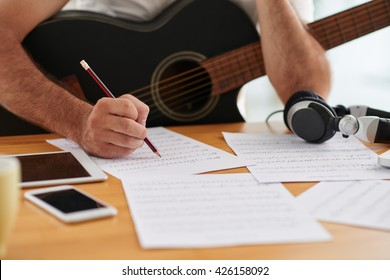 Close-up image of composer examining sheets with notes