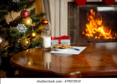 Closeup image of cookies, glass of milk and letter for Santa Claus on table next to burning fireplace and Christmas tree