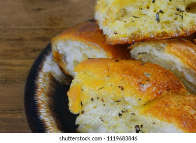 Closeup image of crusty garlic bread with melted butter and spices soaking up the bread on a crockery plate and a wooden table