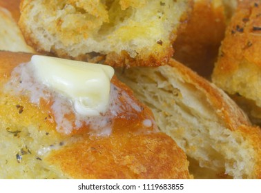 Closeup image of crusty garlic bread with melting butter and spices soaking up the bread