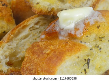 Closeup image of crusty garlic bread with melted butter and spices soaking up the bread