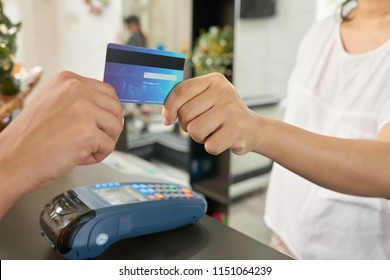 Close-up image of customer paying with card in beauty salon