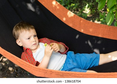 Close-up image of a cute kid lying on the swing.