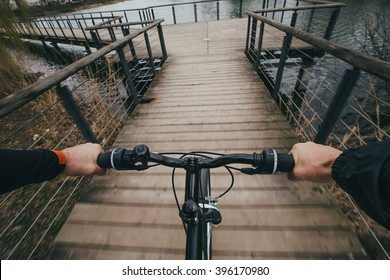 Close-up image of cyclist man hands on handlebar riding bike in park, face is not visible.Young man riding bike in city park near river.View from bikers eyes.