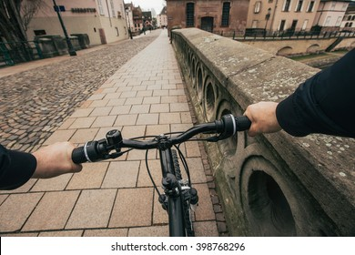 Close-up image of cyclist man hands on handlebar riding bike in city street, face is not visible.Young man riding bike in city bridge near river.View from bikers eyes.