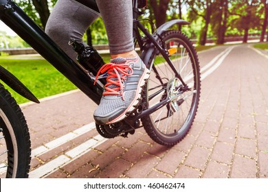 Close-up image of cyclist woman feet riding mountain bike on trail in summer