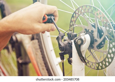Close-up image of cyclist's hand repairs wheel of bicycle