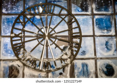 Closeup image of decorated Christmas interior at wall with big clock background.Old rusty big street clock on wall of the building,hotel, store.Old metal clock hanging on the transporent wall.