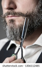 close-up image depicting the act of correcting whiskers with barber scissors