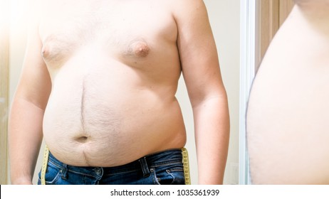 Closeup image of fat man with big belly and gynecomastia looking at reflection in mirror