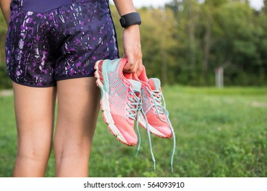 Closeup image of a female athlete with sport coach on her wrist holding sneakers in one hand at the park