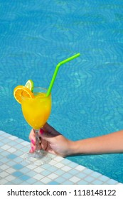 Closeup image of female beauty holding glass of cocktail drink near swimming pool