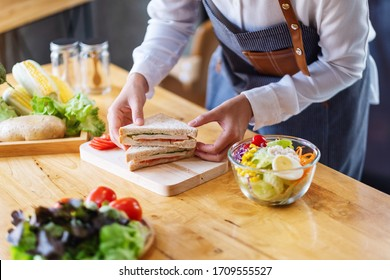 Closeup image of a female chef cooking and holding a piece of whole wheat sandwich in kitchen