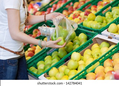 Closeup image of a female customer picking green apples to buy.