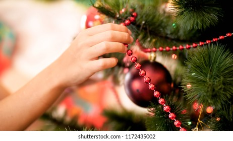 CLoseup image of female hand putting red decorative beads on Christmas tree branches