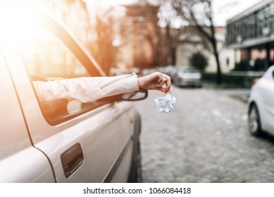 Close-up image of female hand throwing garbage out of car window.