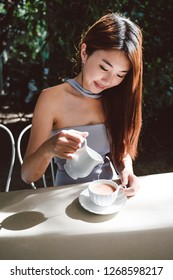 Closeup image of female hands pouring milk and preparing fresh coffee, and preparation concept in the garden, morning coffee before work hard
