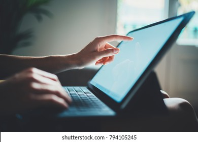 Closeup image of female hands typing on touch screen of modern digital tablet device, businesswoman working from home via portable computer, communication and technology concept
