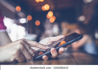 Close-up image of female hands using smartphone at night on coffee shop, searching or social networks concept, hipster woman typing an sms message to his friends