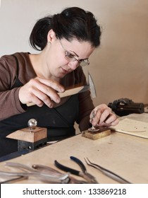 Close-up image of a female jeweler hammering a piece of metal in her workshop. There is an intended motion blur on the hammer.