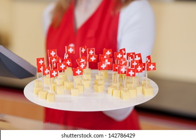 Close-up image of a female worker offering cheese cubes for tasting.