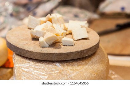 Close-up image of few small pieces of cheese on a wooden board in a market stall.