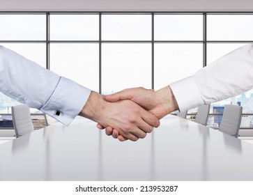 Close-up image of a firm handshake standing for a trusted partnership, modern office space.