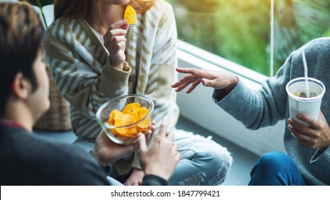 Closeup image of friends drinking and eating potato chips together