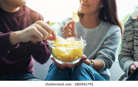 Closeup image of friends sharing and eating potato chips at home party together