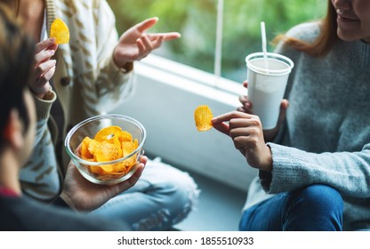 Closeup image of friends talking, drinking and eating potato chips together