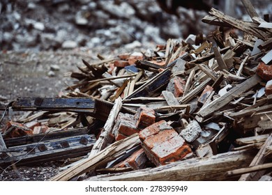 A closeup image of a garbage dump with ruined brick and wooden planks. Concept of disaster, war.