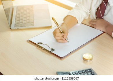 Closeup image of a girl hand writing down on a white blank notebook with laptop and bitcion on wooden table.