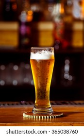 Closeup image of glass with golden unbottled light beer at bar background.