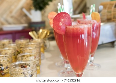 Closeup image of a glass of watermelon smoothie with a grape.