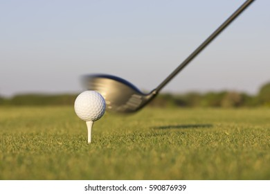 Closeup image of a golf club about to hit a golf ball.