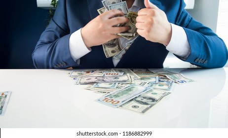Closeup image of greedy covetous businesman filling his pockets with stacks of money