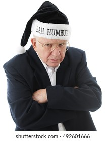 """Close-up image of a grumpy old man in black, wearing a black """"Bah Humbug"""" Santa hat.  On a white background."""