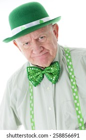 Closeup image of a grumpy senior man dressed all in green.  His suspenders and hat are adorned with shamrocks.  On a white background.