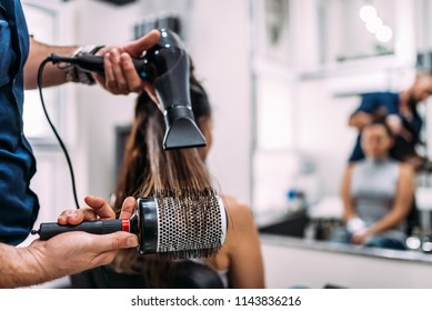 Close-up image of hairdressers hands drying long hair with blow dryer and round brush.