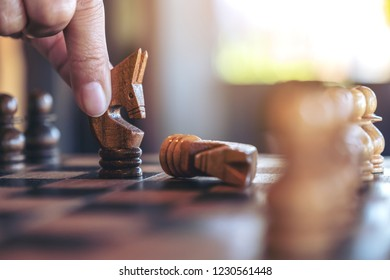 Closeup image of a hand holding and moving a horse to win another horse in wooden chessboard game
