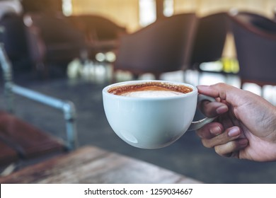 Closeup image of a hand holding a white cup of hot coffee on wooden table in cafe