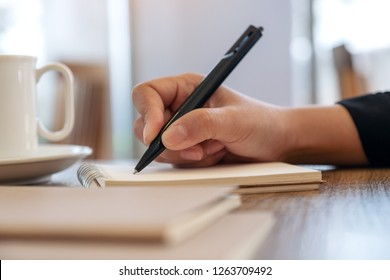 Closeup image of a hand writing on blank notebook with coffee cup on table in cafe
