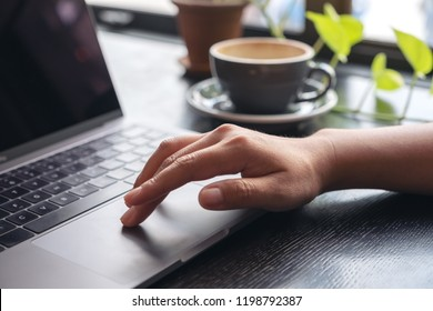 Closeup image of hands using and touching on laptop touchpad with coffee cup on wooden table