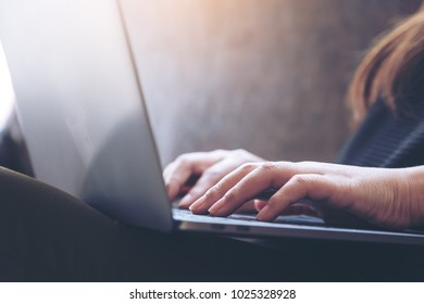 Closeup image of hands working and typing on laptop keyboard on the table