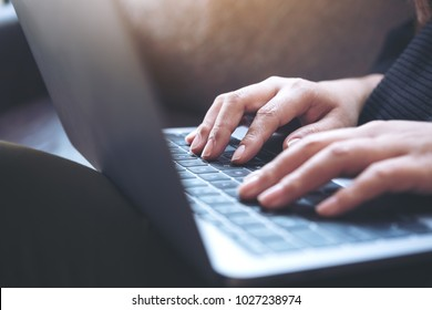 Closeup image of hands working and typing on laptop keyboard while sitting on sofa