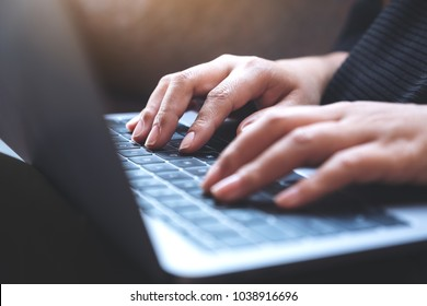 Closeup image of hands working and typing on laptop keyboard with blur background