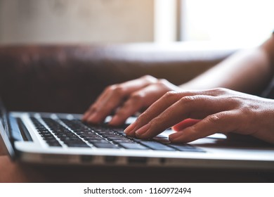 Closeup image of hands working and typing on laptop keyboard on wooden table with blur background