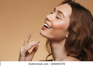 Closeup image of happy beautiful woman 20s with long auburn hair posing on camera in profile with magnificent smile isolated over beige background